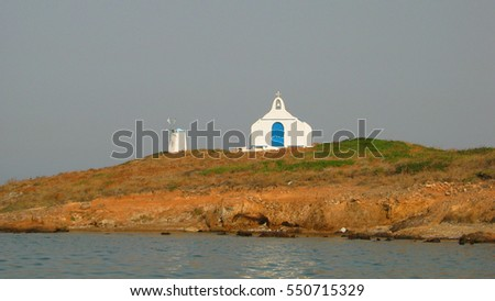 Small island of Vraona with windmill and picturesque small church, Vravrona, Attica, Greece