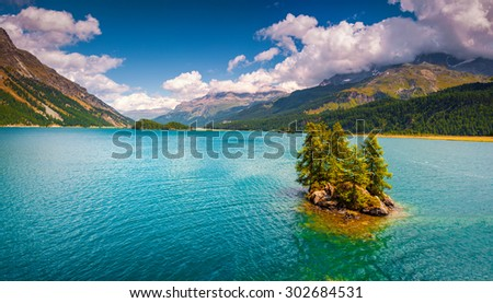 Small island on the Silsersee lake in the Swiss Alps. Segl, Switzerland, Europe.