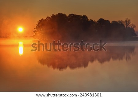 Small island over calm foggy lake water surface during sunrise, Mazury, Poland - stock photo