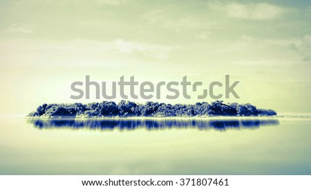 Small island with little bungalows in tropical sea - stock photo
