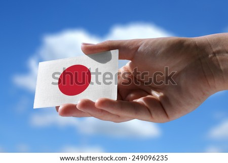 Small Japanese flag against sky with cumulus clouds - stock photo