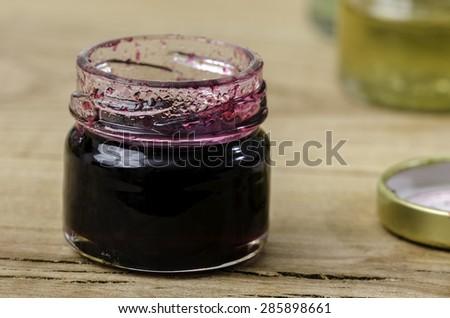 Small jar of blackberry honey over elm wood. - stock photo