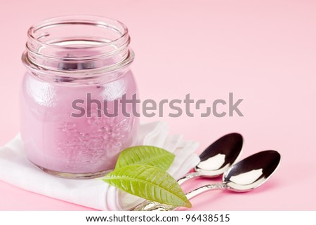small jars with yogurt on rose background with leaves - stock photo