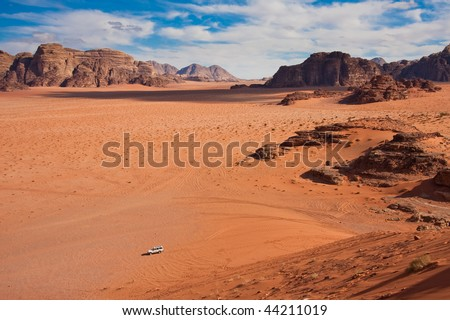 Small jeep in a huge desert of Wadi Rum. Shot from the only massive sand dune. - stock photo