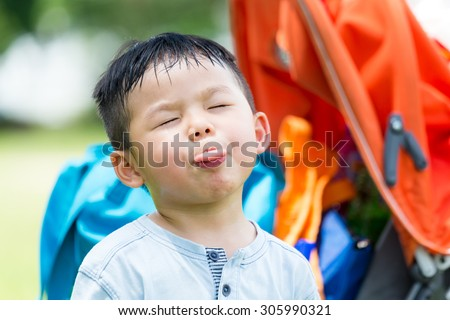 Small kid showing his tongue to make a funny face - stock photo