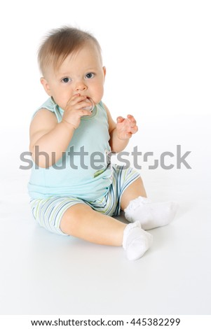 small kid wears blue T-shirt and striped pants full-leight sitting and chewing nipple white background, isolated