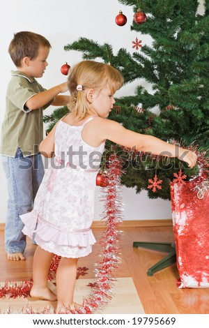 Small kids decorating the christmas tree indoors - stock photo