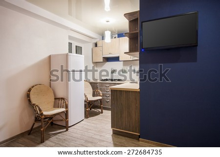 Small kitchenette in a studio, interior lighting - stock photo