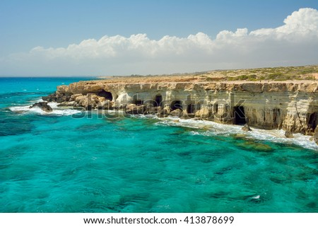 Small lagoon with cyan water and many caves inside coastal rocks in Cape Greco area near Ayia Napa city on Cyprus island. - stock photo