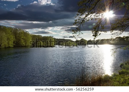 Small lake under dark clouds - stock photo
