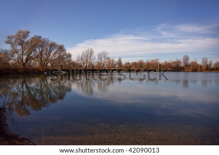 Small Lake with Trees in Autumn, with reflections in the water