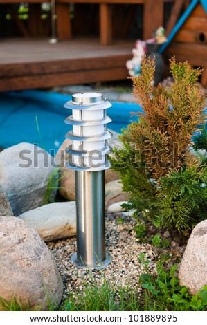small lantern in a garden on the ground - stock photo