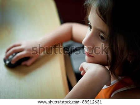 Small latin  girl working with a computer at home - stock photo
