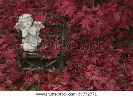 Small lawn ornament surrounded by freshly fallen Japanese Maple leaves. - stock photo