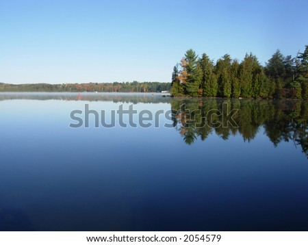 Small layer of morning mist along the surface of a calm blue lake.