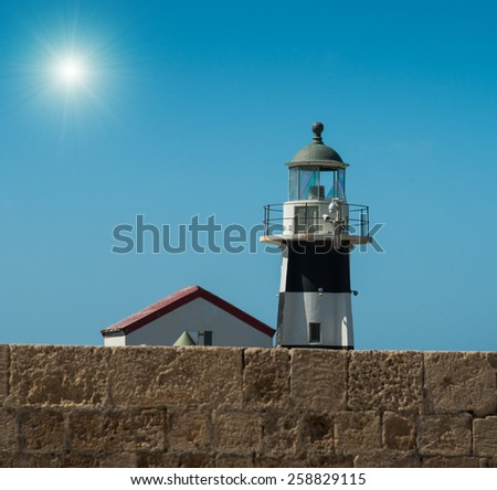 Small lighthouse in sunny afternoon - stock photo