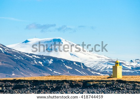 Small lighthouse on an island with mountains in the background - stock photo