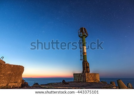 Small lighthouse on the edge of a concrete pier at the starry night in summer - stock photo