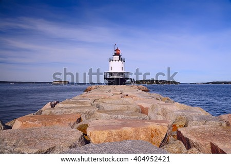 small lighthouse with a glowing white light in the bay, the ocean bay, the road from the huge rough stones leading to it. Sunny day. Blue sky and small clouds.  Portland. America, Maine,  - stock photo