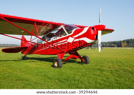 Small lightweight private airplane standing on airfield grass - stock photo