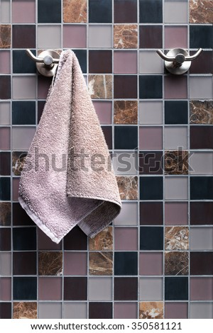 Small lilac terry towel for hands hanging on a towel rack in the bathroom on a square lined ceramic tile background. - stock photo
