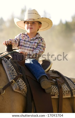 Small little boy riding his horse in evening light - stock photo