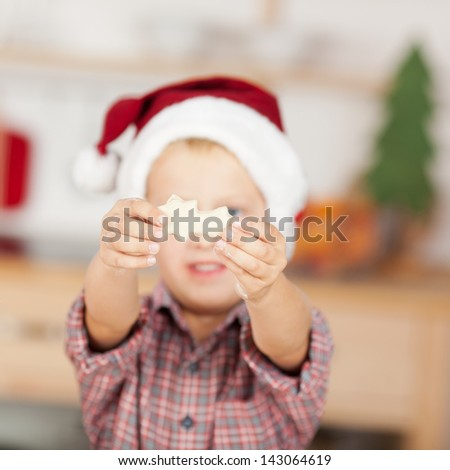 Small little boy wearing Christmas hat shows the gingerbread - stock photo