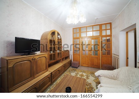 Small living room with a sofa, a cabinet and a carpet on the floor - stock photo