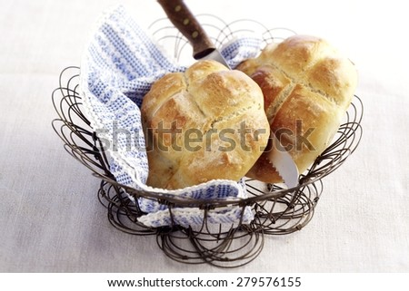 Small loaves of traditional Roman Bread in a basket on a grey tablecloth - stock photo