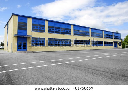 Small local two story high old school building made of yellow bricks and asphalt courtyard for the kids. - stock photo