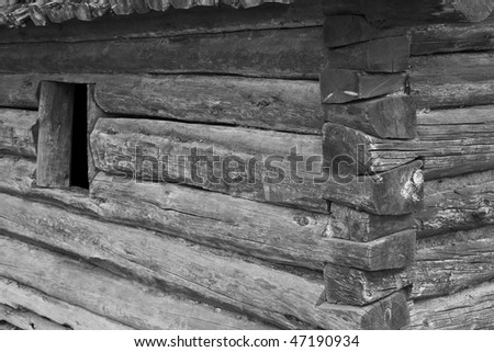 Small log cabin with open window close up done in black and white - stock photo