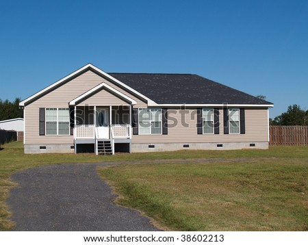 Small low income manufactured home with a covered porch and vinyl siding. - stock photo