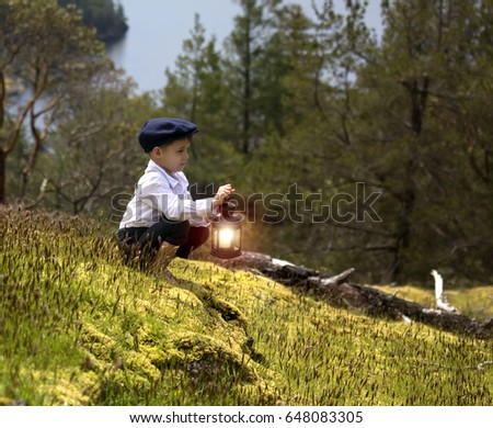 small male child on a hill holding a candle lit lantern.