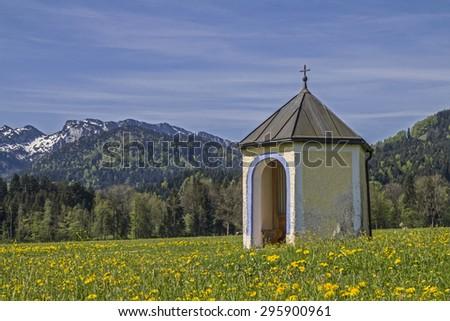 Small meadows chapel before the mountain group of Benediktenwand - stock photo