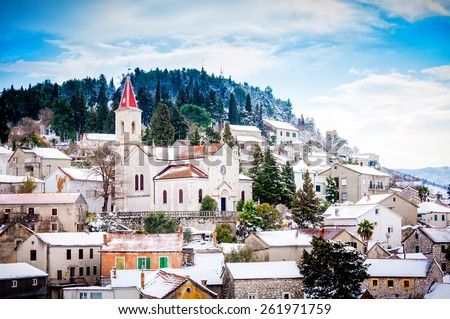 Small Mediterranean town on the slopes of hill with a church on top, covered in snow - stock photo