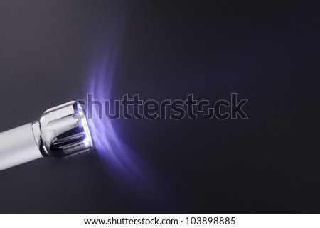 small metal LED flashlight on a gray surface