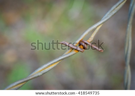 Small metal twist of rusted barbed wire on fence line. - stock photo
