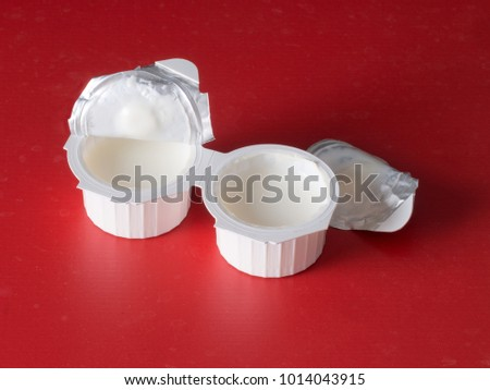 Small milk, coffee creamer pots on red. Mono portions, for catering etc.
