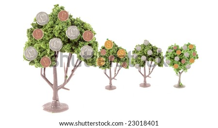 small miniature forest growing copper and silver dollars, yen, euros and  pound coins ... British pound tree is in front showing strength in currency exchange - stock photo