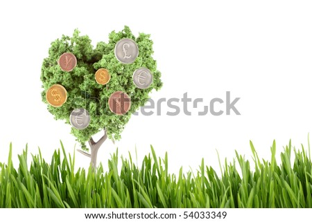 small miniature tree growing silver gold and copper, coins in different currency like dollars, yen, euro, and the British pound with grassy foreground - stock photo