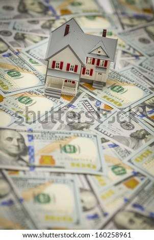 Small Model House on Newly Designed U.S. One Hundred Dollar Bills. - stock photo