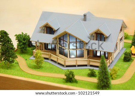 Small model of cottage with exterior - trees, bushes and path - stock photo