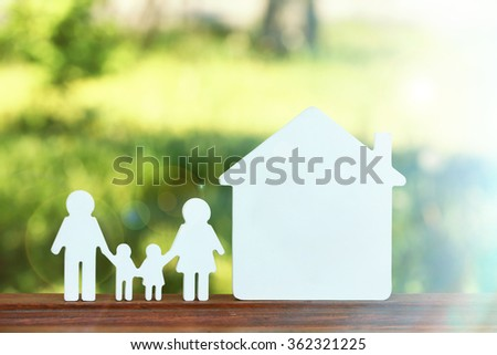 Small model of house and family on blurred background