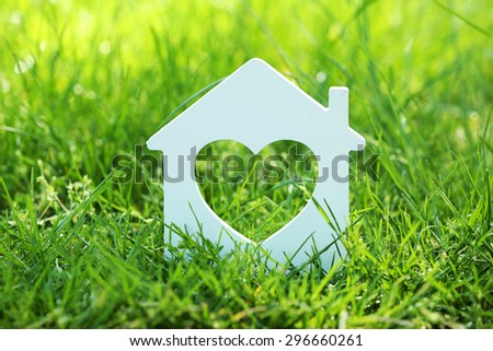 Small model of house over green grass background