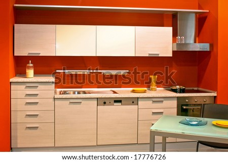 Small modern kitchen in red wall apartment