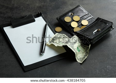 small money in my wallet on a black background near notepad with pen.The concept of poverty - stock photo