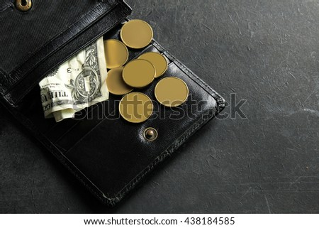 small money in my wallet on black background.The concept of poverty - stock photo