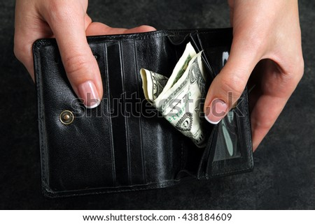 small money in the wallet on the black background in the hands of women.The concept of poverty - stock photo