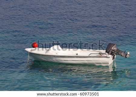 Small motor boat on the silent sea - stock photo