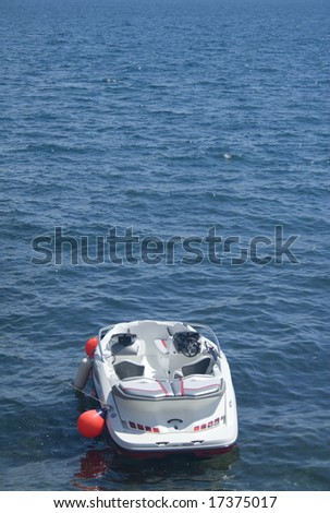Small motorboat floating alone near buoy - stock photo